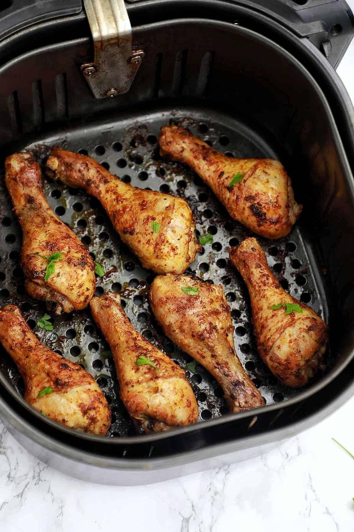 cooked frozen chicken drumsticks in air fryer basket.