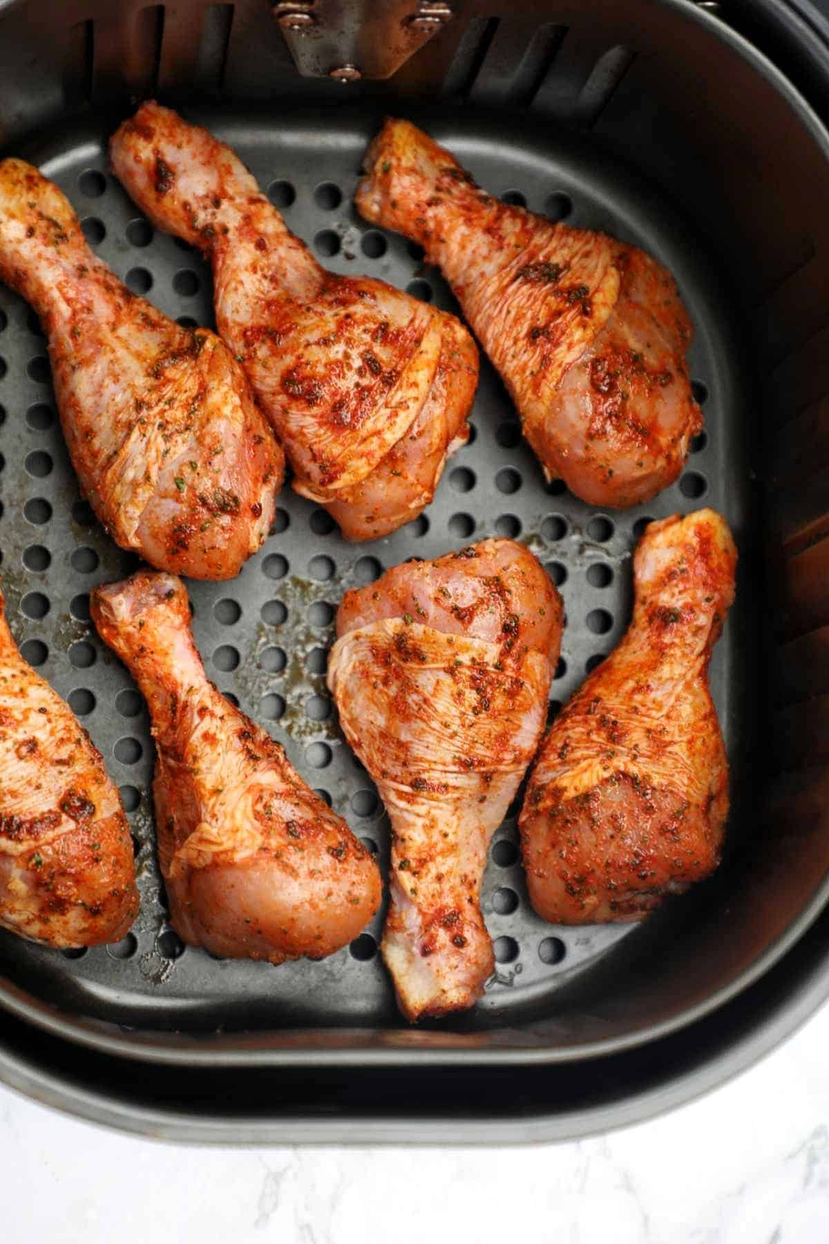 the marinated drumsticks in the air fryer basket.